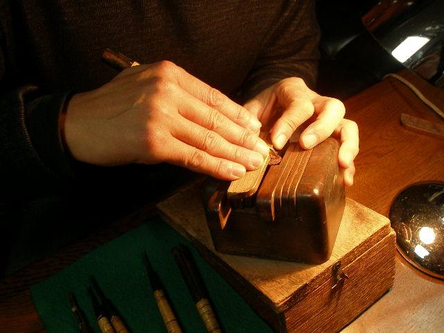 真心こめて彫刻中! 当店は昭和40年創業以来、地域の皆様に支えられ  「手彫り印鑑の店」として営業しております。  手彫り独特の深い味わい、緻細な表現は匠の技術。  機械彫刻では再現不能で偽造防止にも効果的です。